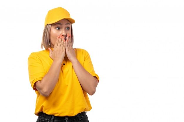 Una vista frontal de mensajería femenina en camisa amarilla gorra amarilla y jeans negros posando con expresión de sorpresa en blanco
