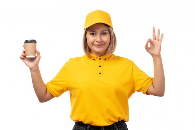 Una vista frontal de mensajería femenina en camisa amarilla gorra amarilla y jeans negros posando sosteniendo café sonriendo en blanco