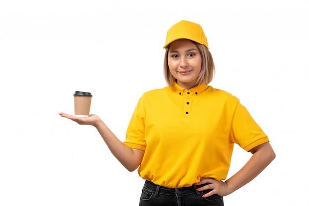 Una vista frontal de mensajería femenina en camisa amarilla gorra amarilla y jeans negros sonriendo sosteniendo la taza de café en blanco