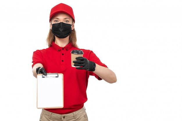 Una vista frontal de mensajería femenina en camisa roja gorra roja guantes negros con café en blanco