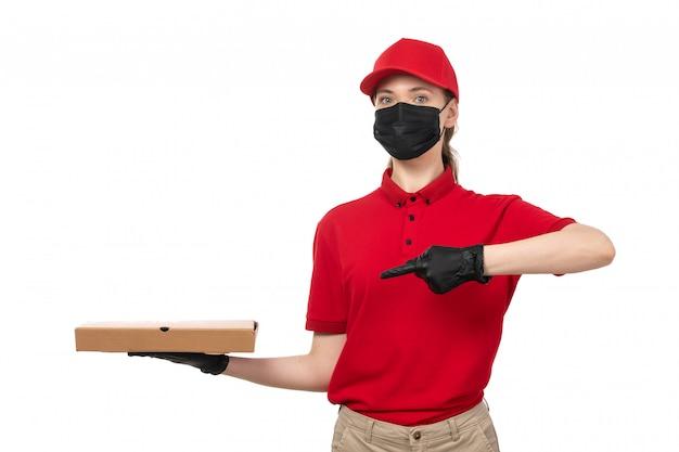 Una vista frontal de mensajería femenina en camisa roja gorra roja guantes negros y máscara negra con caja de pizza señalando en blanco