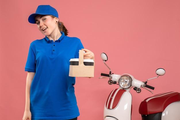 Vista frontal de mensajería femenina con entrega de café en el piso rosa trabajo servicio de entrega trabajadora mujer bicicleta uniforme trabajo