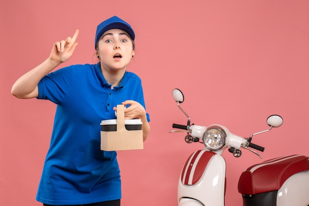 Vista frontal de mensajería femenina con entrega de café en el servicio de entrega de trabajo rosa trabajo trabajador mujer uniforme de bicicleta