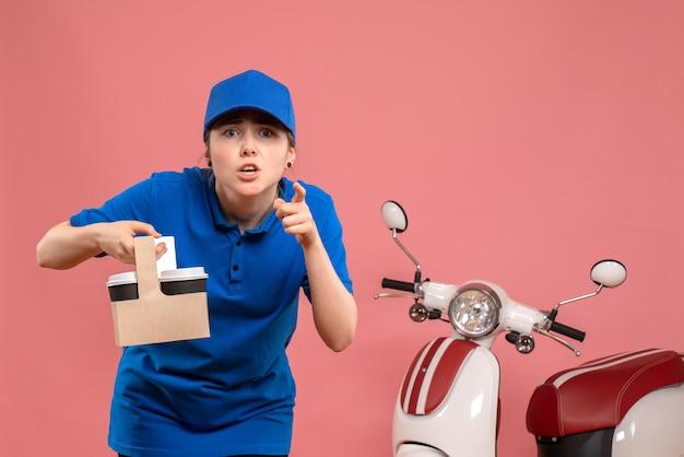Vista frontal de mensajería femenina con entrega de café en el trabajo de color rosa trabajador de servicio de entrega mujer trabajo uniforme en bicicleta