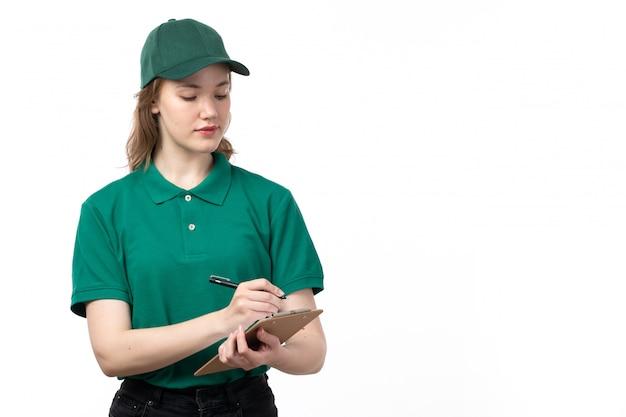 Una vista frontal de mensajería femenina joven en uniforme verde sosteniendo el bloc de notas escribiendo pedidos