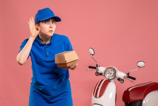 Vista frontal de mensajería femenina con pequeño paquete de comida escuchando en rosa trabajo servicio uniforme de entrega de trabajo bicicleta trabajador pizza mujer