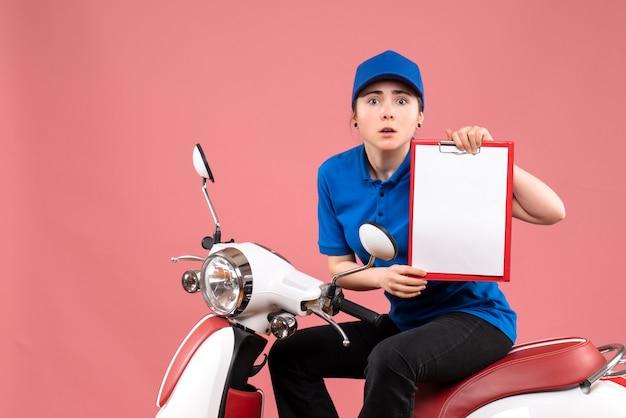 Vista frontal de mensajería femenina sentada en bicicleta con nota de archivo en color rosa uniforme de servicio de entrega de alimentos trabajador de trabajo