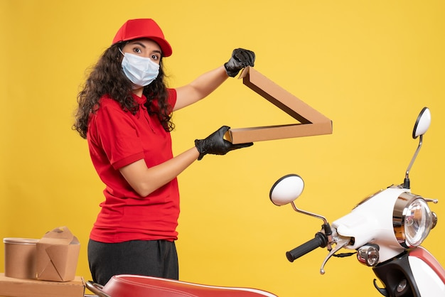 Vista frontal de mensajería femenina en uniforme rojo abriendo caja de pizza sobre fondo amarillo trabajador entrega covid- trabajo de virus de servicio pandémico