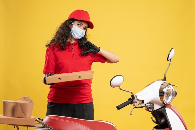 Vista frontal de mensajería femenina en uniforme rojo con caja de pizza sobre fondo amarillo trabajador de servicio covid- trabajo de virus pandémico