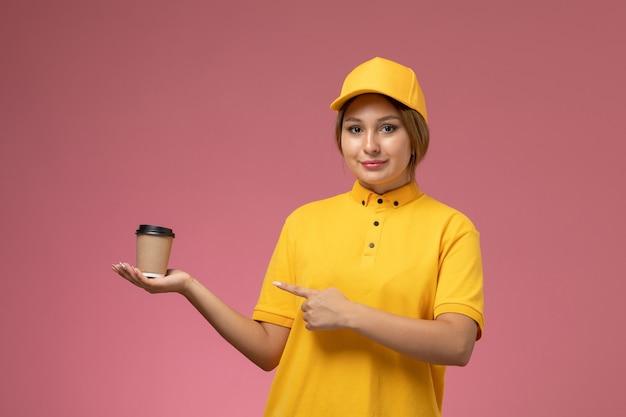 Vista frontal mensajero femenino en uniforme amarillo capa amarilla sosteniendo una taza de café de plástico con una leve sonrisa sobre fondo rosa trabajo de entrega uniforme foto en color femenino