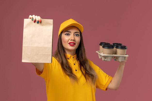 Vista frontal del mensajero femenino en uniforme amarillo y gorra sosteniendo tazas de café marrón y paquete de comida en la pared rosa