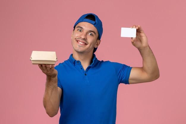 Vista frontal, mensajero, macho joven, en, uniforme azul, capa, tenencia, pequeño, entrega, paquete de comida, y, blanco, tarjeta, en, pared rosa claro