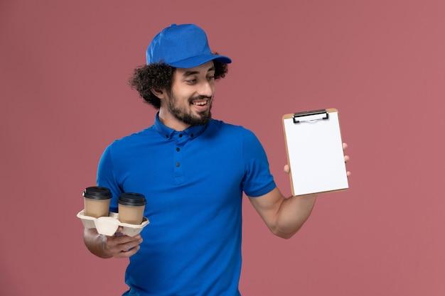 Vista frontal del mensajero masculino en gorra uniforme azul con tazas de café de entrega y bloc de notas en sus manos en la pared rosa