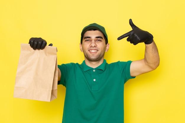 Vista frontal mensajero masculino joven en camisa verde gorra verde con paquete de entrega con sonrisa en amarillo