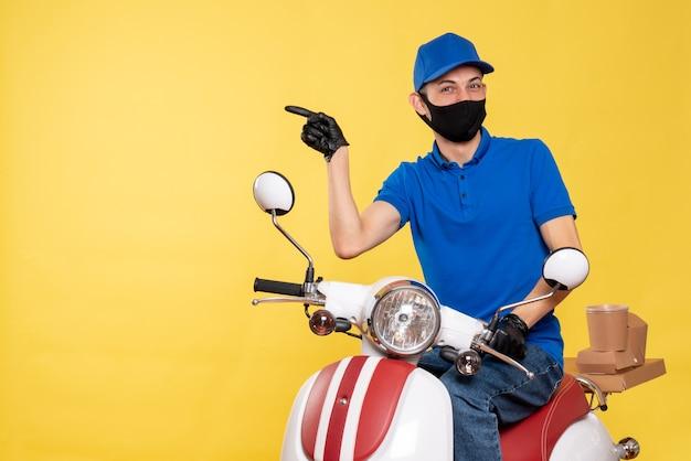 Vista frontal mensajero masculino joven en uniforme azul y máscara sobre fondo amarillo