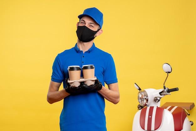 Vista frontal mensajero masculino en máscara sosteniendo café en uniforme de trabajo amarillo covid- servicio de trabajo pandemia de entrega