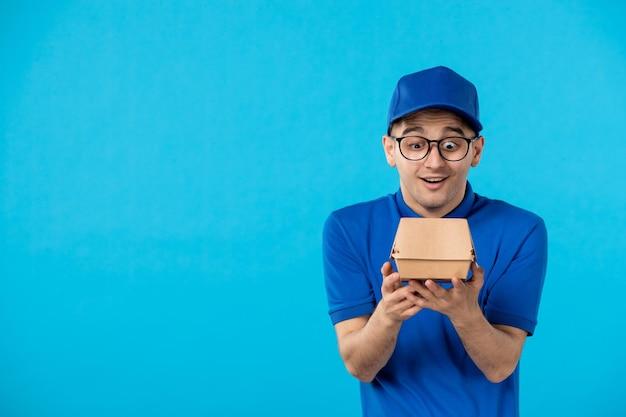 Vista frontal del mensajero masculino con paquete de comida de entrega azul