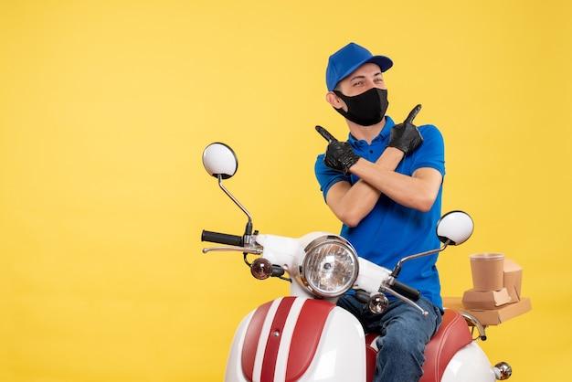 Vista frontal mensajero masculino sentado en bicicleta con máscara en servicio amarillo entrega pandémica covid- trabajo uniforme de trabajo