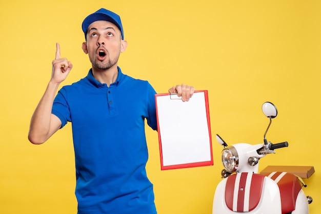 Vista frontal mensajero masculino sosteniendo nota de archivo en color amarillo trabajador servicio uniforme trabajo emoción