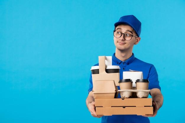Vista frontal del mensajero masculino en uniforme azul con café y pizza azul