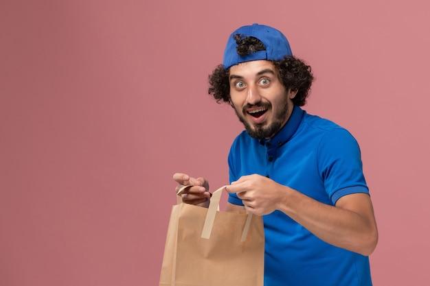 Vista frontal mensajero masculino en uniforme azul y capa con paquete de comida de papel de entrega en la pared rosa uniforme de servicio de entrega masculino