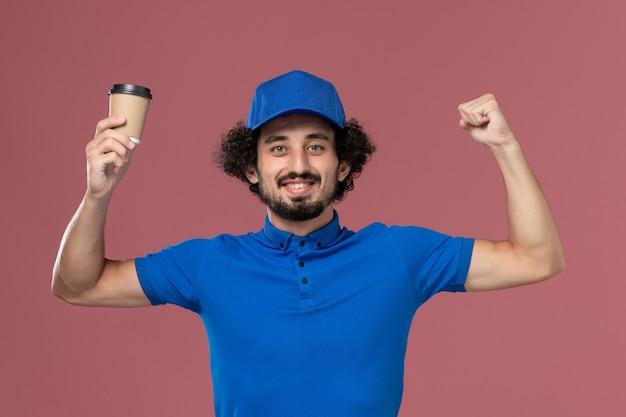 Vista frontal del mensajero masculino en uniforme azul y gorra con taza de café de entrega en sus manos en la pared rosa