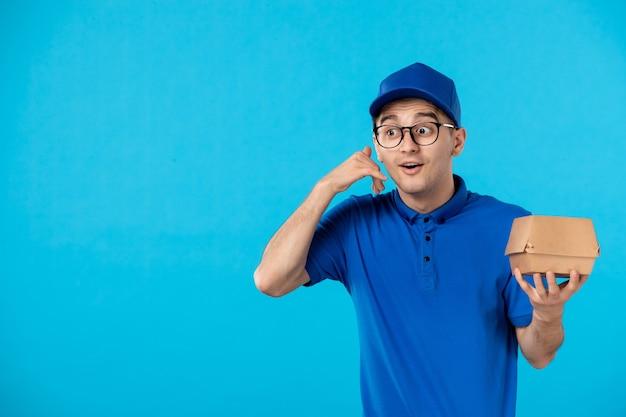 Vista frontal del mensajero masculino en uniforme azul con pequeño paquete de comida en azul