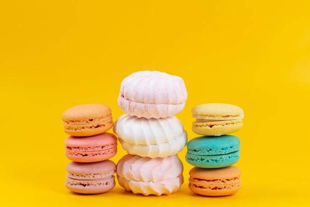 Una vista frontal de merengues y macarons deliciosos y pasteles horneados aislados en amarillo, confitura de galleta de pastel