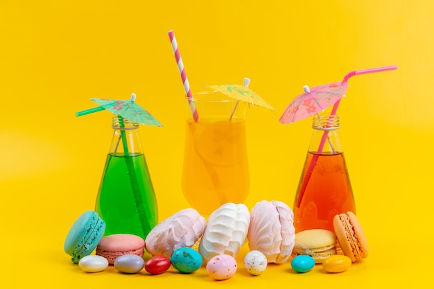 Una vista frontal de merengues y macarons junto con cócteles en amarillo, pastel de color galleta