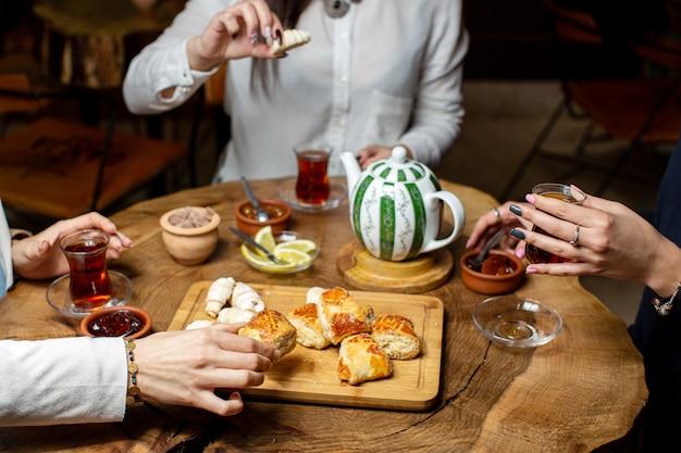 Una vista frontal de la mesa de té junto con pasteles y galletas