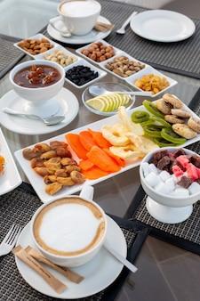 Vista frontal de una mesa de té con mermelada de café, nueces, dulces, frutos secos y caramelos en el restaurante durante el día, mesa de té dulce fuera