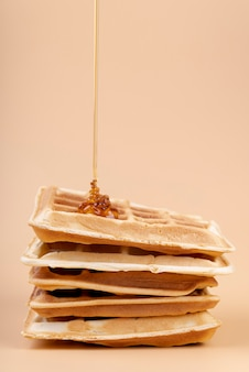 Vista frontal de miel goteando en la pila de waffles