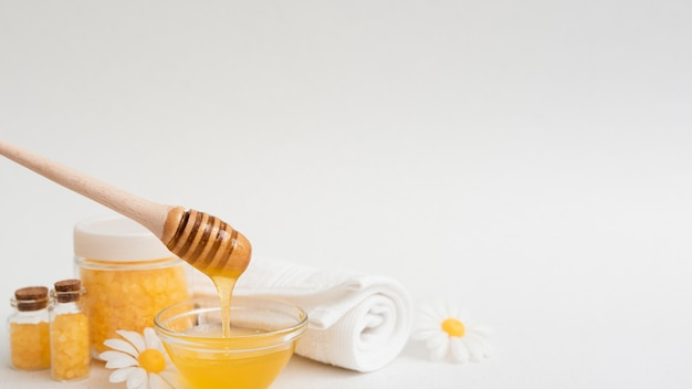 Vista frontal de miel y otros elementos esenciales del spa.