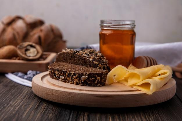 Vista frontal de la miel en un tarro con pan negro y queso sobre un soporte con nueces sobre un fondo de madera