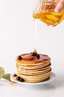 Vista frontal miel vertida sobre torre de panqueques en placa con arándanos