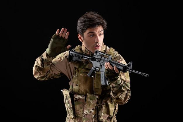 Vista frontal del militar en uniforme apuntando con su rifle de tiro de estudio en la pared negra