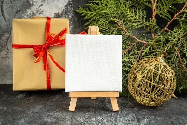 Vista frontal mini lienzo sobre caballete de madera rama de pino adornos de navidad mini regalo sobre fondo gris
