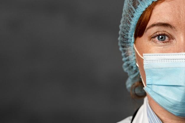 Vista frontal de la mitad de la cara de la doctora con máscara médica y espacio de copia