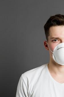 Vista frontal de la mitad de la cara del hombre con una máscara médica