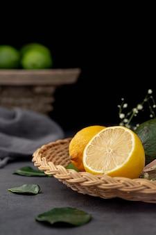 Vista frontal de la mitad de limón en un plato con hojas