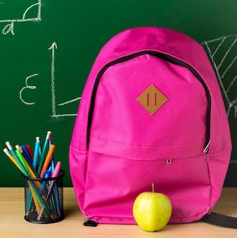 Vista frontal de la mochila para el regreso a la escuela con manzana y lápices.