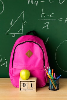 Vista frontal de la mochila de regreso a la escuela con manzana y lápices