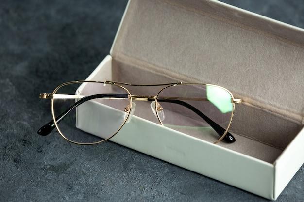 Una vista frontal modernas gafas de sol ópticas dentro de una pequeña caja en el gris