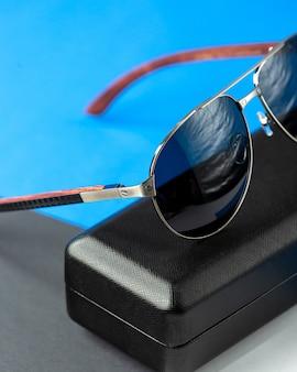 Una vista frontal modernas gafas de sol oscuras en el azul oscuro