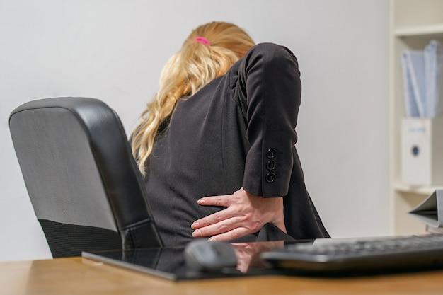 Vista frontal molesta empresaria sintiendo dolor de espalda sentado en la silla de oficina tocando el músculo dolorido