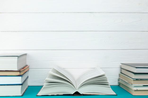 Vista frontal montones de libros con espacio de copia