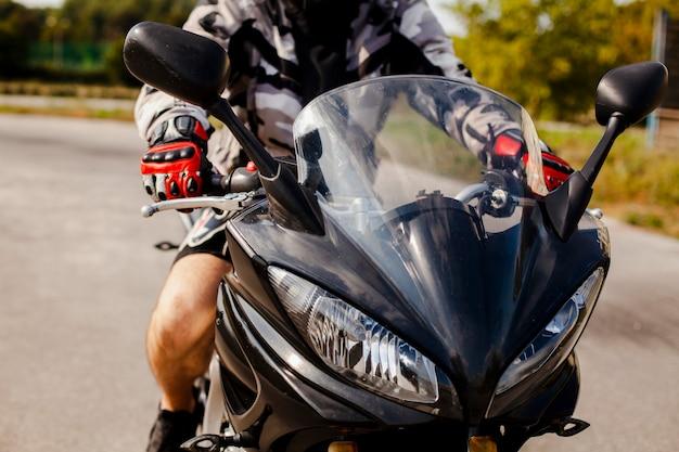 Vista frontal de la moto con el motorista encendido