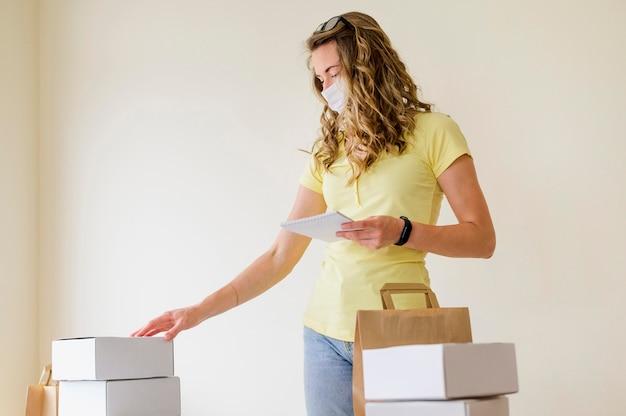 Vista frontal mujer adulta comprobando productos pedidos