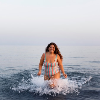 Vista frontal de la mujer en el agua en la playa
