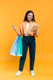 Vista frontal, de, mujer, agujereado, tableta, y, bolsas de compras